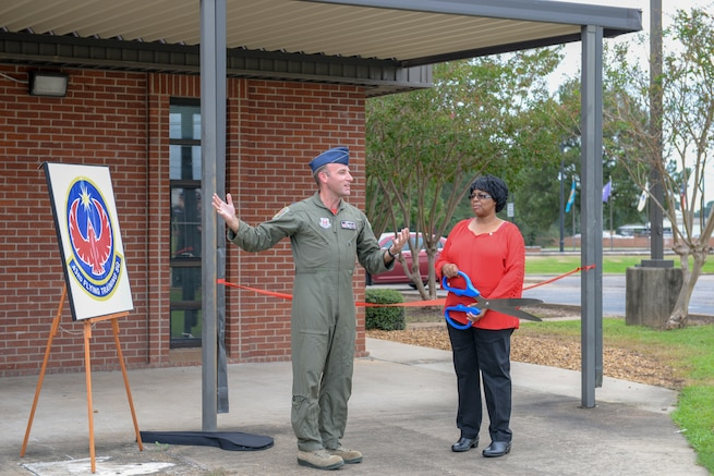 Lt. Col. Tom McElhinney, 43rd Flying Training Squadron commander, and Elaine Hobson, former 43rd Flying Training Squadron secretary welcomes attendees during the dedication ceremony for the squadron's new building Sept. 28, 2018, on Columbus Air Force Base, Mississippi. Hobson recently retired after 17 years of civil service. (U.S. Air Force photo by Airman Hannah Bean)