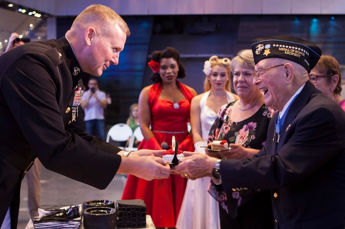 "Brig. Gen. Bradley S. James, commanding general of 4th Marine Aircraft Wing, presents a slice of cake to retired Chief Warrant Officer 4 Hershel ""Woody"" Williams, the last surviving Medal of Honor recipient from the Battle of Iwo Jima, during Williams' 95th birthday party at the National World War II Museum, Oct. 2, 2018. Williams enlisted in the Marine Corps Reserve in 1943 and served in the Battle of Iwo Jima with 21st Marines, 3rd Marine Division in 1945. (U.S. Marine Corps photo by Lance Cpl Tessa D. Watts)"