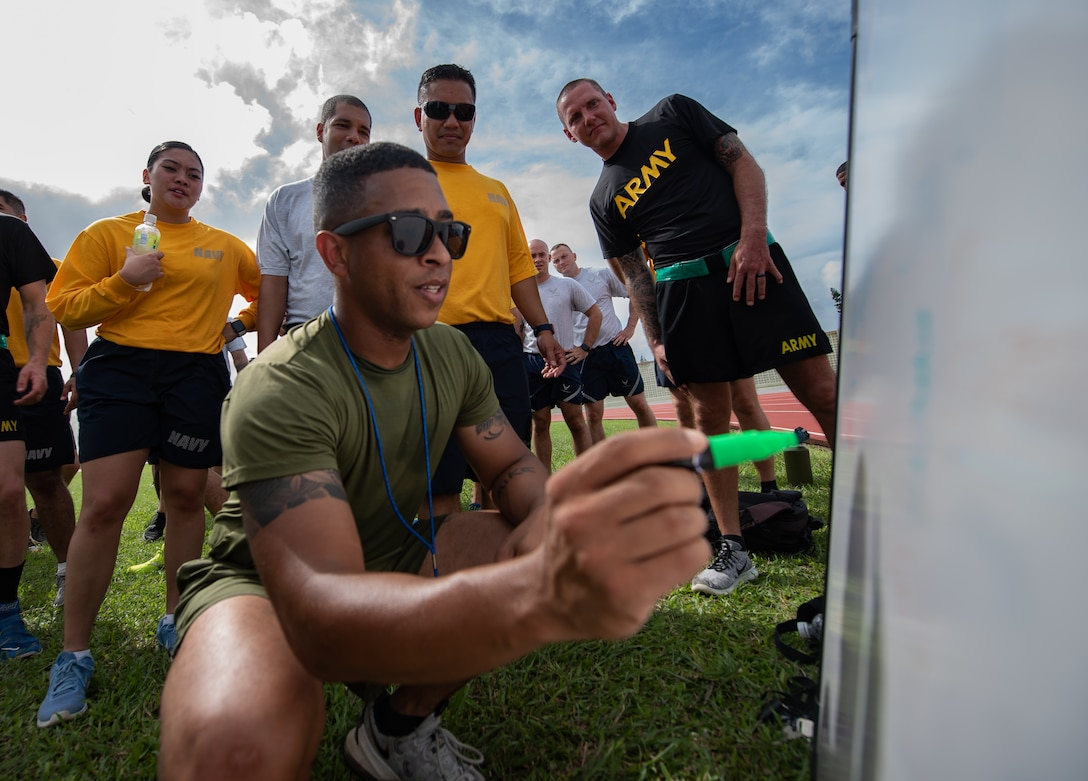U.S. Marine Corps 1st Sgt. Michael Collins, Okinawa Joint Experience instructor, updates each team's score during the Okinawa Joint Fitness Challenge Sept. 26, 2018, at Kadena Air Base, Japan. After calculating points from the push-up challenge, combat fitness challenge and tug-of-war, the Green Team was determined the winner of the OJFC. (U.S. Air Force photo by Staff Sgt. Micaiah Anthony)