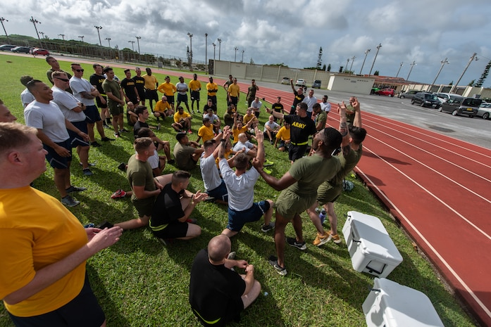 Members of the Green Team celebrate after being announced the winner of the Okinawa Joint Fitness Challenge Sept. 26, 2018, at Kadena Air Base, Japan. The OJFC was designed to mimic obstacles and challenges faced in the battlefield such as sprinting, running ammunition cans, transporting wounded personnel to safety and tossing simulated grenades. Each team competed for the best time, however the final challenge brought all four teams together. (U.S. Air Force photo by Staff Sgt. Micaiah Anthony)
