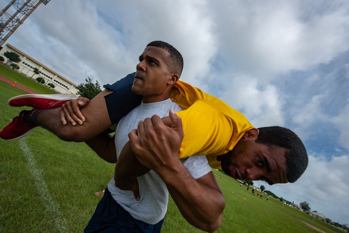 U.S. Air Force Staff Sgt. Thomas Nollie carries U.S. Navy Petty Officer 2nd Class Jesse Pedrero, both Okinawa Joint Experience Green Team students, during the Okinawa Joint Fitness Challenge Sept. 26, 2018, at Kadena Air Base, Japan. The OJFC was designed to mimic obstacles and challenges faced in the battlefield such as sprinting, running ammunition cans, transporting wounded personnel to safety and tossing simulated grenades. Each team competed for the best time, however the final challenge brought all four teams together. (U.S. Air Force photo by Staff Sgt. Micaiah Anthony)