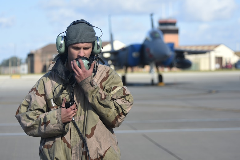 """An Airman assigned to the 492nd Fighter Squadron communicates with pilots before departure during the """"FURIOUS 48"""" readiness exercise at Royal Air Force Lakenheath, England, Oct. 1, 2018. Exercises like this provide both aircrew and support personnel stationed at RAF Lakenheath the experience needed to maintain a ready force capable of ensuring the collective defense of the NATO alliance. (U.S. Air Force photo by Airman 1st Class Christopher S. Sparks)"""