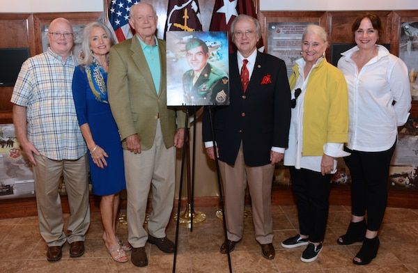"""(From left) Bubba Brice, Frances Younger, John F. Younger Jr., Charles M. Younger, """"Chica"""" Younger and Galeana Younger pose with a portrait of Bobby Joe Younger, a World War II bombardier killed in action in 1944. The family were presented with Younger's military awards posthumously received from the Department of the Army."""