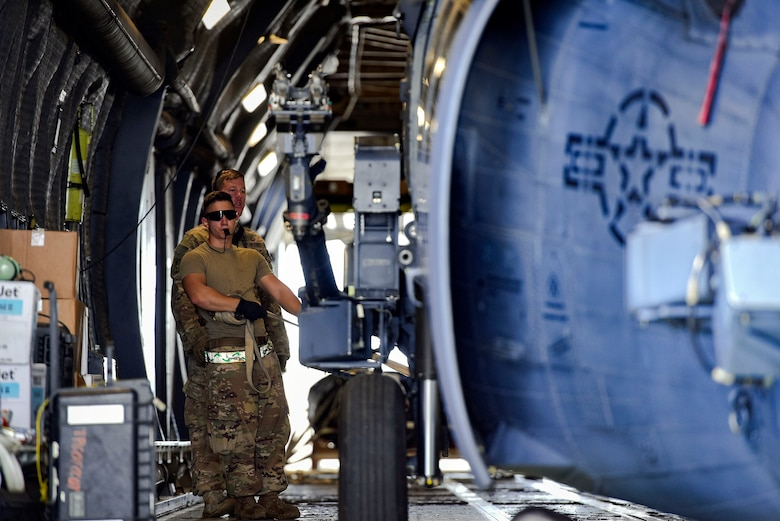 Airman 1st Class Thomas Kervian, 41st Helicopter Maintenance Unit HH-60G Pave Hawk crew chief, guides a helicopter to be secured in a C-5 Galaxy prior to a deployment, Sept. 26, 2018, at Moody Air Force Base, Ga. The 41st RQS and the 41st Helicopter Maintenance Unit will provide combat search and rescue capabilities and maintenance operations in a forward deployed location. (U.S. Air Force photo by Senior Airman Greg Nash)