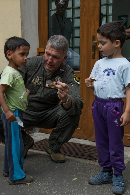 U.S. Air Force Reserve Col. Robert VanHoy, 307th Bomb Wing commander, gives a wing coin to a boy at the Children's Center orphanage on Sept. 13, 2018, Ostrava, Czech Republic. The children's home is a nongovernment medical organization with a nonstop service and is designed generally for children ages new born to 3. (U.S. Air Force photo by Master Sgt. Greg Steele)