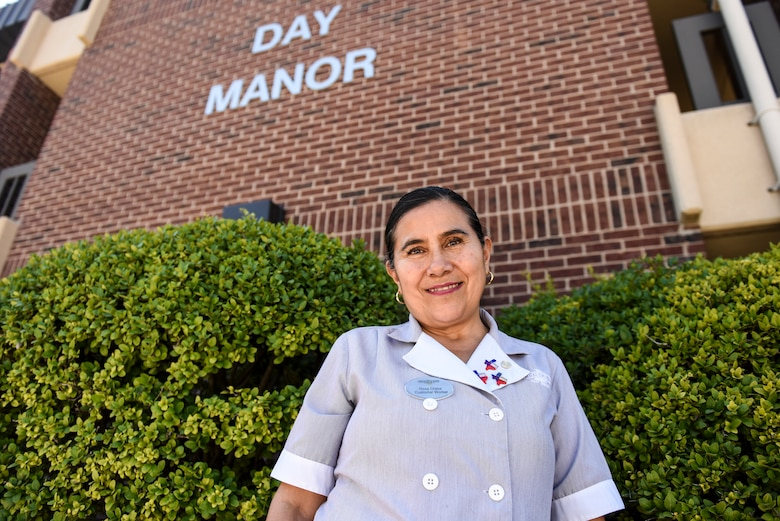 Angelo Inn housekeeper, Rosa Drake, stands before Day Manor where she works on Goodfellow Air Force Base, Texas, Sept. 24, 2018.  Drake has worked for Air Force lodging for five years. (U.S. Air Force photo by Aryn Lockhart/Released)