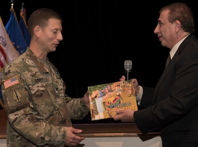 Michel Zajur, founder Virginia Hispanic Chamber of Commerce founder, presents a book to U.S. Army Col. Rick Zampelli, 128th Aviation Brigade commander, during the National Hispanic Heritage Month ceremony at Joint Base Langley-Eustis, Virginia., Oct. 4, 2018.