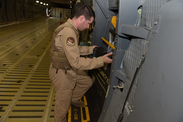 Tech. Sgt. David Bass, 22nd Airlift Squadron C-5M Super Galaxy loadmaster, affixes armor to the inside of one of the troop doors of a C-5 at Travis Air Force Base, Calif., Sept. 12. The armor is required to ensure air crew safety while the aircraft fly's through hostile environments. (U.S. Air Force photo by Tech. Sgt. James Hodgman)