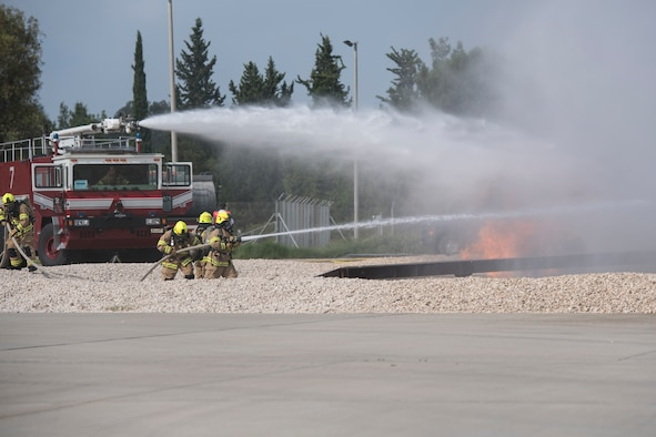 The 39th Civil Engineer Squadron training managers light a simulted aircraft fire during an exercise at Incirlik Air Base, Turkey, Aug. 7, 2018. The simulated aircraft fire is used to keep the fire fighters properly trained and prepared in case of a real-world incident. (U.S. Air Force photo by Staff Sgt. Kimberly Nagle)