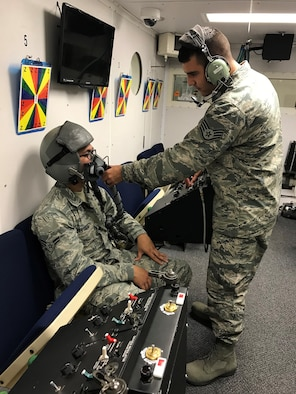 Staff Sgt. Luciano Cattaneo, an Aerospace and Operational Technician and NCOIC of Administration/Scheduling at the United States Air Force School of Aerospace Medicine, helps a student get fitted for an oxygen mask in the hyperbaric chamber. (Courtesy Photo)