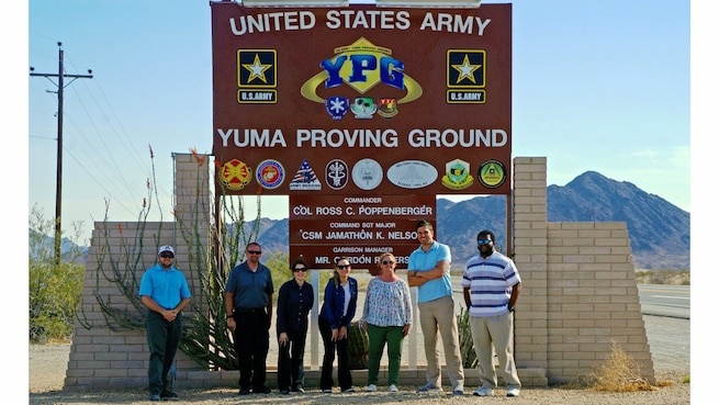 Seven people stand in front of a large sign at the entrance to Yuma Proving Ground.