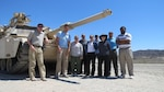 Nine people stand in front of an Abrams tank on a sunny day in the desert.