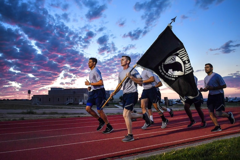 Airmen run with the POW/MIA flag in the early morning hours during a 24-hour run at Schriever Air Force Base, Colo., Sept. 19, 2018. Airmen from various squadrons continuously ran with the POW/MIA flag in 30 minute intervals, with more than 70 participants carrying the flag for a total of 120 miles. (U.S. Air Force photo by Kathryn Calvert)