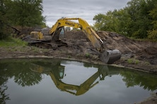 heavy machinery breaches river embankment