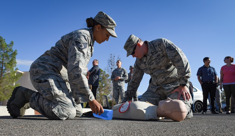 Staff. Sgt. Jordan Holmes, Nevada Test and Training Range occupational safety team member, and Tech. Sgt. Jeremy Cunningham, NTTR target shop flight chief, perform CPR on a dummy during a fire drill at Nellis Air Force Base, Nevada, Oct. 4, 2018. Air Force units are required to have trained personnel who can perform CPR and use an Automated External Defibrillator. (U.S. Air Force photo by Airman 1st Class Andrew D. Sarver)