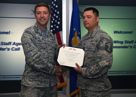 Maj. Steven P. Jordan, 62nd Comptroller Squadron commmander, presents a Bronze Star Medal award to Master Sgt. Kevin R. Peterson, 62nd Airlift Wing command post superintendent, inside the 4th Airlift Squadron on Joint Base Lewis-McChord, Wash. Sep. 21, 2018.