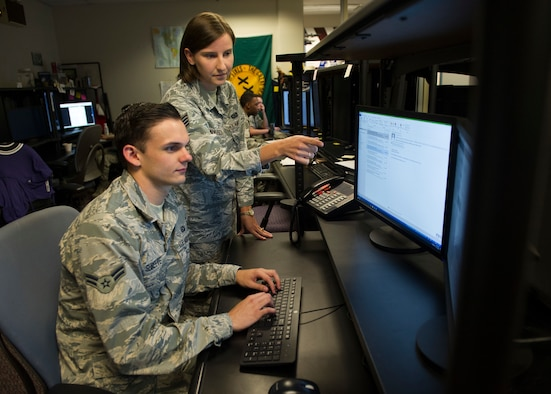 Staff Sgt. Elizabeth Caulfield, Signals Analysis Squadron scientific and technical signals analyst, mentors an Airman on mission operations July 11, 2018 at the National Air and Space Intelligence Center on Wright-Patterson Air Force Base, Ohio. Caulfield was named one of the 12 Outstanding Airmen of the Year for the Air Force. (U.S. Air Force photo/ Senior Airman Michael Hunsaker)