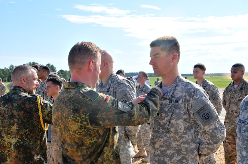 A Germany army officer pins German jump wings on the uniform of a U.S. soldier.