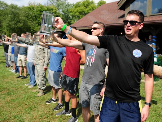 Members of the National Air and Space Intelligence Center compete in a Stein Raise competition during the National Air and Space Intelligence Center's Oktoberfest on Wright-Patterson Air Force Base, Ohio, Sept. 21, 2018. During the competition participants were challenged to see who would be the last one holding the mug of water.. (U.S. Air Force photo by Senior Airman Michael Hunsaker)