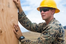 U.S. Marine Corps Cpl. Braiden M. Wadin, a combat engineer with Bravo Company, 7th Engineer Support Battalion, Task Force Koa Moana (TF KM), holds a wooden wall during the construction of a South West Asia hut during the TF KM Mission Rehearsal Exercise, at Marine Corps Base Camp Pendleton, Calif., July 18, 2018. The exercise confirmed TF KM is capable of cross cultural interaction, instruction, and relationship building while training alongside partner nations in order to meet Theater Security Cooperation engagement objectives. (U.S. Marine Corps photo by Staff Sgt. Gabriela Garcia)