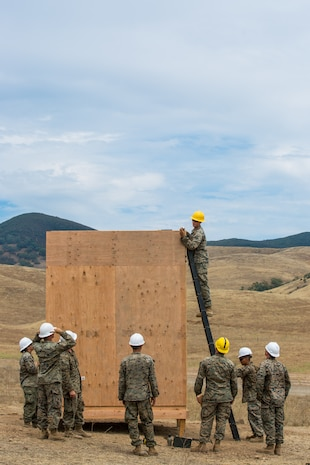 U.S. Marine Corps Cpl. Braiden M. Wadin, top, and other Marine combat engineers with Bravo Company, 7th Engineer Support Battalion, Task Force Koa Moana (TF KM), participate in the construction of a South West Asia hut during the TF KM Mission Rehearsal Exercise, at Marine Corps Base Camp Pendleton, Calif., July 18, 2018. The exercise confirmed TF KM is capable of cross cultural interaction, instruction, and relationship building while training alongside partner nations in order to meet Theater Security Cooperation engagement objectives. (U.S. Marine Corps photo by Staff Sgt. Gabriela Garcia)