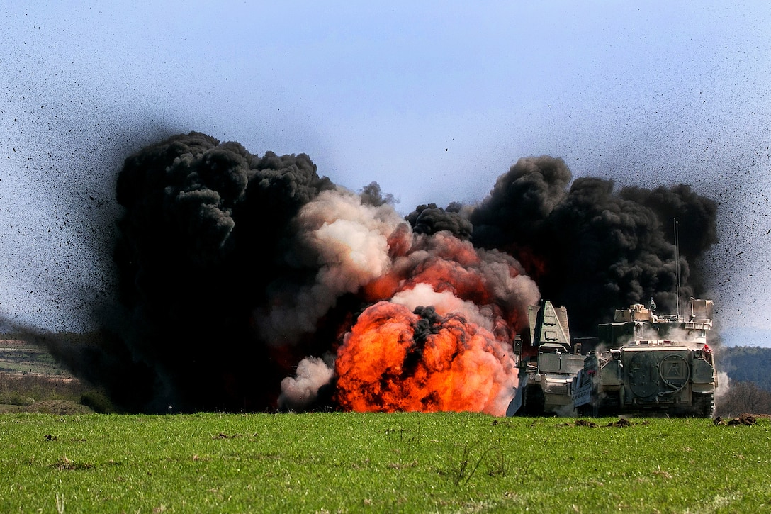 Black clouds of smoke flank a fireball from a detonation in a field.