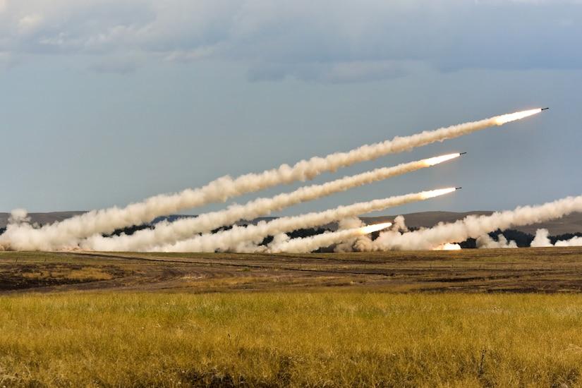 Several rockets shoot across a field, creating smoke trails.