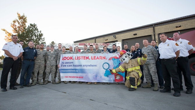"""Firefighters from the 92nd Civil Engineering Squadron pose with Sparky the fire dog for the upcoming national Fire Prevention Week at Fairchild Air Force Base, Washington, Oct. 3, 2018. This year's Fire Prevention Week's campaign is """"Look. Listen. Learn. Be aware. Fire can happen anywhere,"""" which aims to educate the public about basic but essential ways to quickly and safely escape a home fire. (U.S. Air Force photo/Senior Airman Ryan Lackey)"""