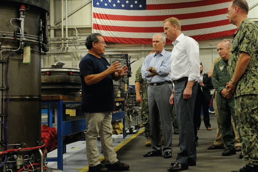 Deputy Defense Secretary Patrick M. Shanahan talks to people in utility room with an American flag on a wall.