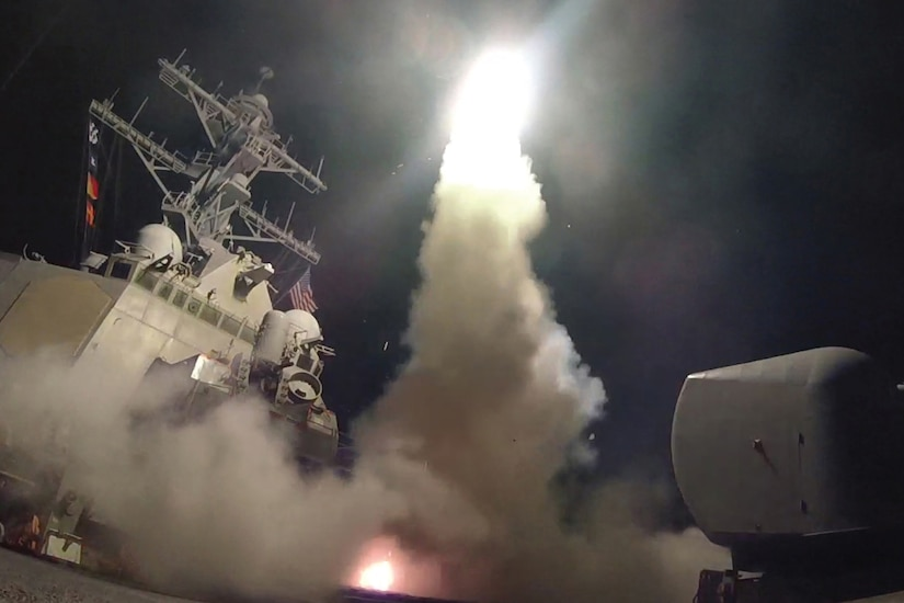A missile launches from a ship at night.