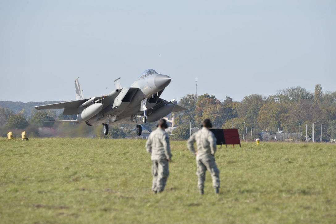 U.S. Airman watch as a U.S. Air Force F-15C Eagle fighter jet lands for the first time on Ukrainian soil to participate in CLEAR SKY 2018, Oct. 6.