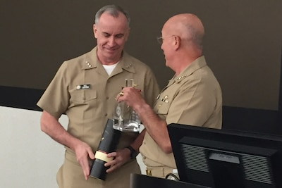 Navy Adm. Kurt Tidd passes the Old Goat Award decanter to Vice Adm. Bill Lesher during an unofficial ceremony at the Washington Navy Yard.