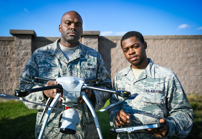 Staff Sgt. Jason Holmes, 51st Civil Engineer Squadron requirements and optimization technician, left, and Senior Airman Herman Stribling, 51st CES Engineer Technician, pose for a photo with a small unmanned aircraft system on Osan Air Base, Republic of Korea, Oct. 3, 2018.