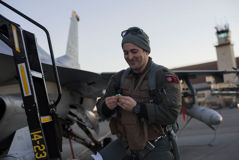 U.S. Air Force Capt. Mark Onorato, the 13th Fighter Squadron activity security manager, inspects his ear protection before climbing into an F-16 Fighting Falcon during Exercise Red Flag-Alaska 19-1, at Eielson Air Force Base, Alaska, Oct. 6, 2018. RF-A 19-1, held Oct. 4 to 19, is slated to train more than 1,000 personnel and 60 aircraft in a simulated air combat environment optimizing personnel's abilities and honing acquired skill sets. (U.S. Air Force photo by Airman 1st Class Collette Brooks)