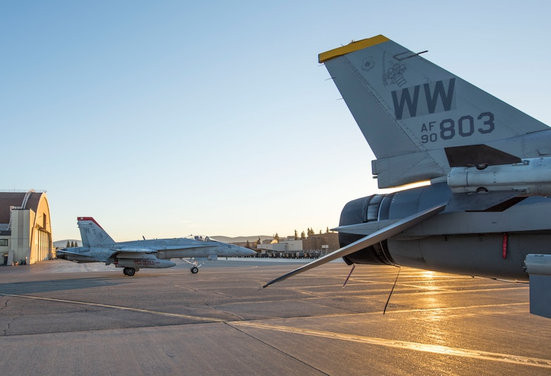 A Marine F/A-18 Hornet aircraft with the Marine Fighter Attack Squadron 232 from Miramar, California, taxis by a 14th Fighter Squadron F-16 Fighting Falcon from Misawa Air Base, Japan, during Exercise Red Flag-Alaska 19-1, at Eielson Air Base, Alaska, Oct. 6, 2018. For more than two decades, the joint-tactical combat employment exercise focused on ally development and cohesion. U.S. military branches and armed services of multiple countries around the world came together to exchange tactics, operations techniques and procedures to improve interoperability. (U.S. Air Force photo by Airman 1st Class Collette Brooks)