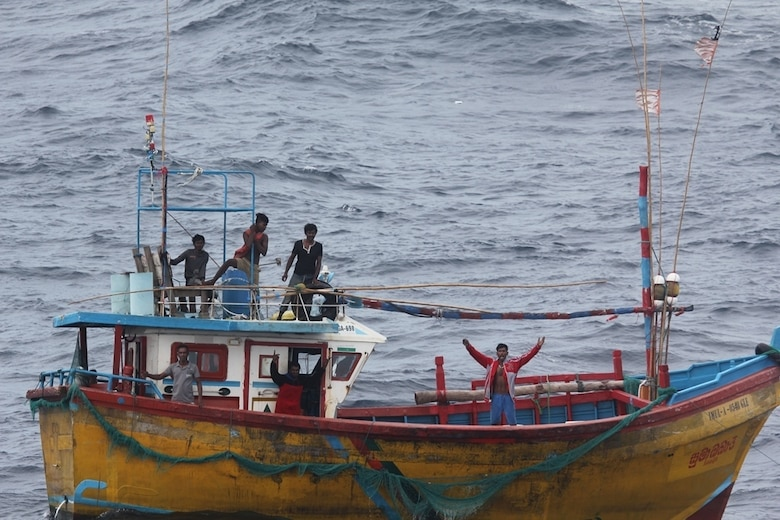 INDIAN OCEAN (Oct. 7, 2018) Stranded Sri Lankan fisherman signal the Arleigh Burke-class guided missile destroyer USS Decatur (DDG 73) for assistance. After providing food and water, Decatur contacted the Sri Lankan authorities who came and towed the stranded vessel back to port. Decatur is forward deployed to the U.S. 7th Fleet area of operations in support of security and stability in the Indo-Pacific region.