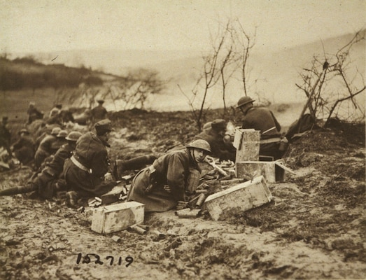"""National Guard Soldiers of the 165th Infantry (formerly the 69th Regiment, New York National Guard) prepare to move forward with weapons at the ready during an attack at Landres-et-St. Georges in October 1918. The 165th Infantry fought as part of the 42nd """"Rainbow"""" Division during St. Mihiel in September and Meuse-Argonne in October, part of the American Expeditionary Force 100 days offensive that brought an end to World War I."""