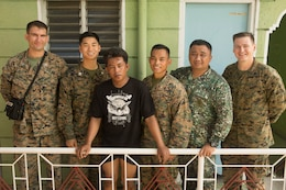 U.S. Marine Corps Capt. Mark Hanford and Sgt. Nicholas Elston, U.S. Navy Lt. Maundo Lee and Brian Bonzo, and Philippine Marine Corps Capt. Rodilson Malic, pose for a photo with Philippine local, Bryan S. Rodriguez, who they assisted after a motorcycle crash in Ternate, Cavite, Philippines, Oct. 2, 2018.