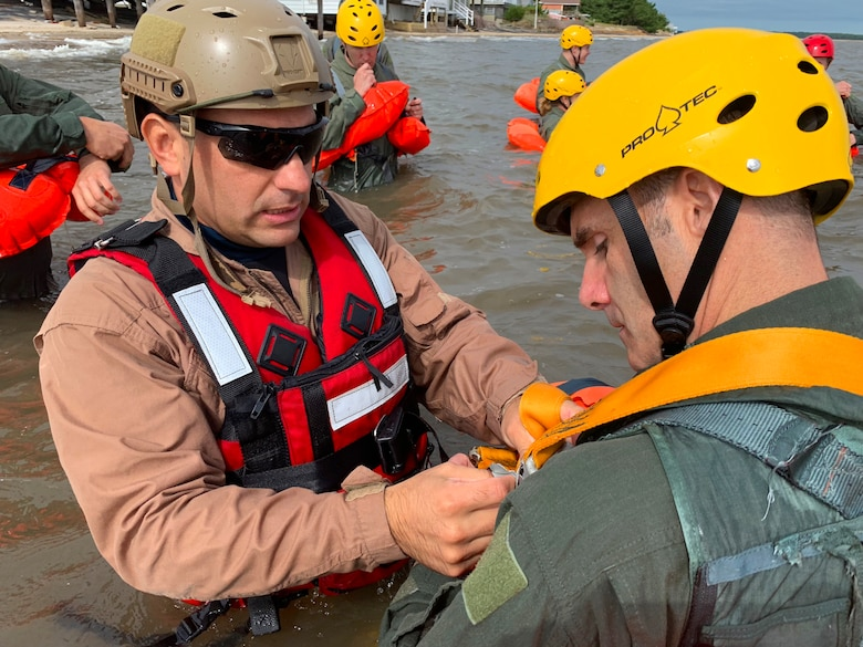 Tech. Sgt. Joseph Monreal, 436th Civil Engineer Squadron Survival, Evasion, Resistance and Escape instructor, teaches an Airman how to properly secure his flotation device during water survival training Sept. 27, 2018, at Bowers Beach, Del. The training provides aircrews with the skills and knowledge they need to survive if forced to egress over water.