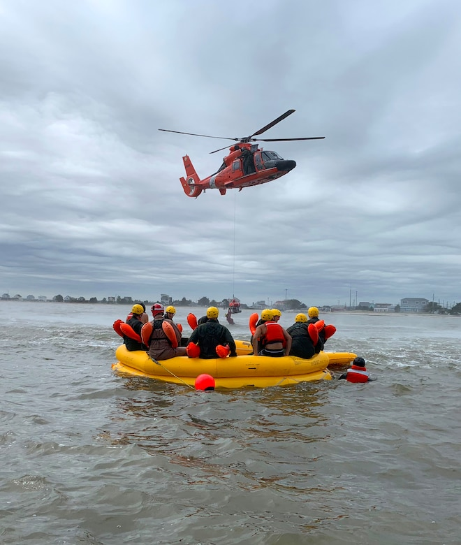 Airmen completing water survival training watch from a raft as a Coast Guard HH-65 Dolphin helicopter lifts a simulated survivor from the Atlantic Ocean Sept. 27, 2018, approximately 200 yards from the coast of Bowers Beach, Del. The Coast Guard rescue crew secured each Airman one by one and hoisted them into the aircraft to simulate a water rescue.