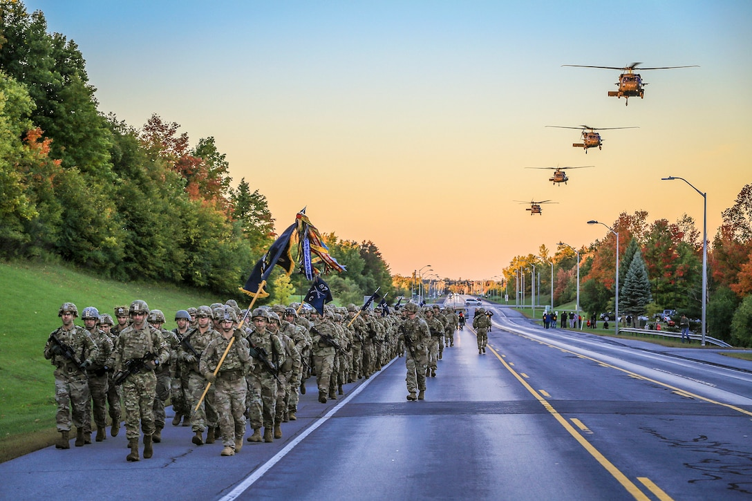 Soldiers march in formation on a road as helicopters fly in a line overhead.
