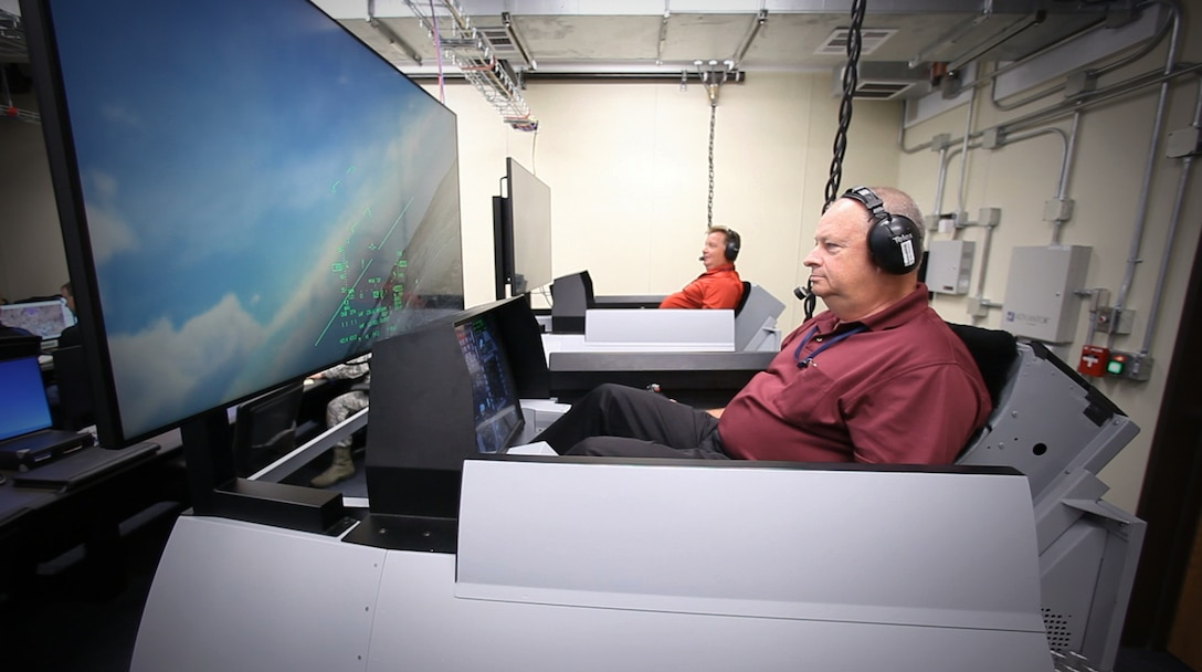 Scott Carpenter and Donald Simones, both subject matter experts in the Air Force Research Laboratory's 711th Human Performance Wing, fly virtual F-16s in Deployable Tactical Trainers. The live aircraft were able to see and interact with the virtual players during Phase III of the Secure Live Virtual Constructive Advanced Training Environment (SLATE) demonstration at Nellis Air Force Base, Nevada, in September. (U.S. Air Force photo/William Graver)