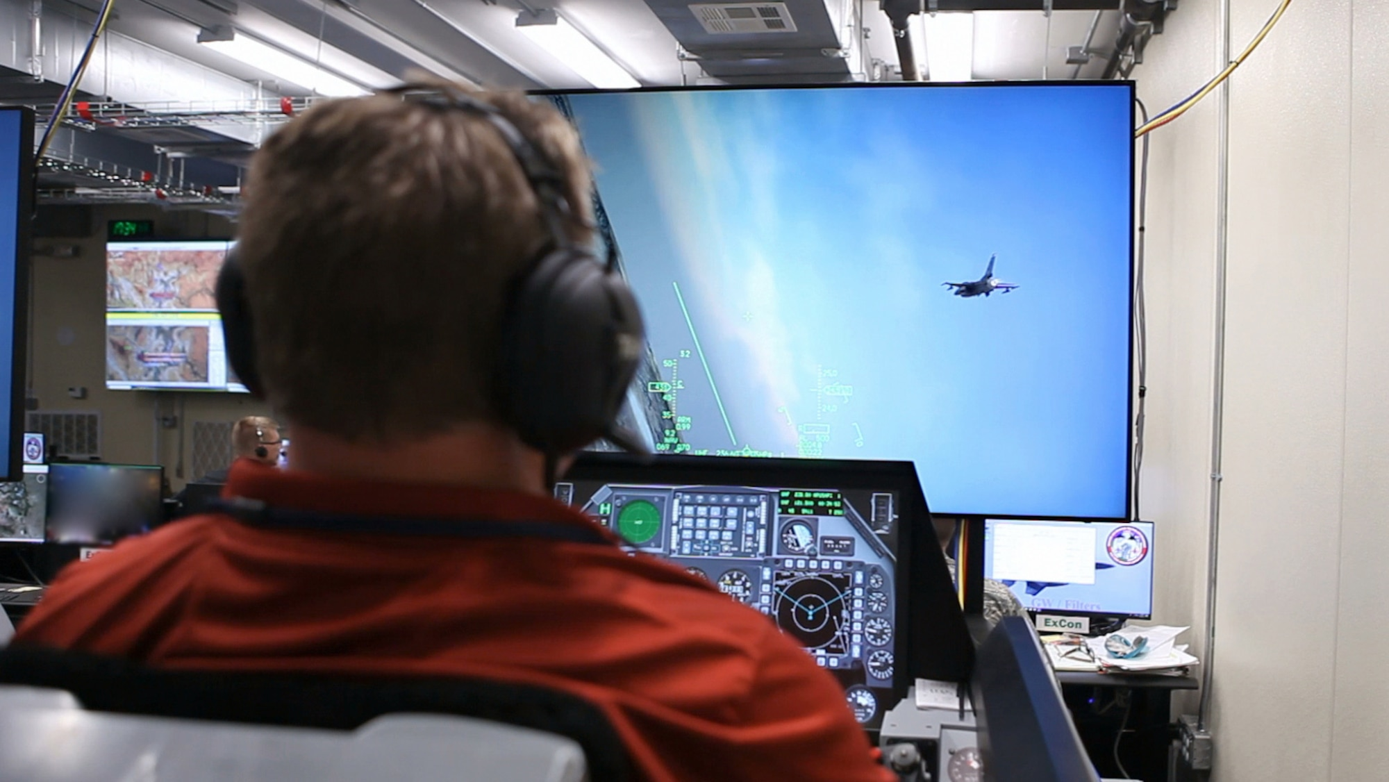 Donald Simones, a subject matter expert in the Air Force Research Laboratory's 711th Human Performance Wing, flies a virtual F-16 in a Deployable Tactical Trainer during the Secure Live Virtual Constructive Advanced Training Environment (SLATE) Phase III capstone demonstration at Nellis Air Force Base, Nevada in September. The live aircraft, such as the one shown on the screen, were able to see and interact with the virtual players like Simones during the demonstration. (U.S. Air Force photo/William Graver)