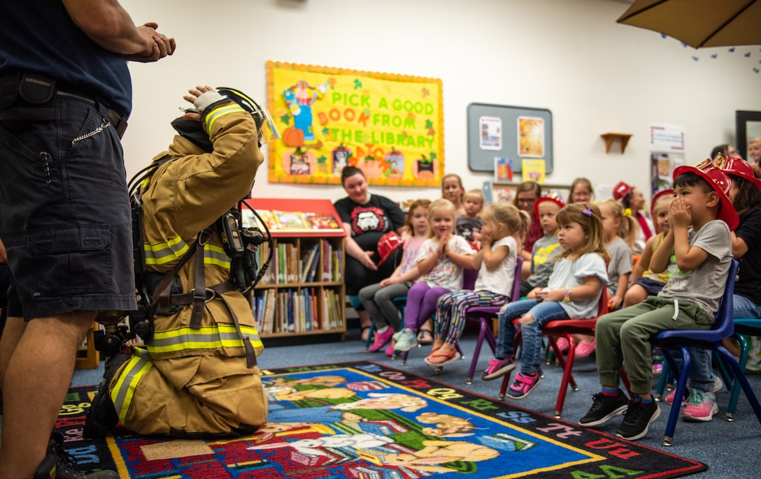 Luke Air Force Base firefighters demonstrate the proper wear of firefighting equipment during their visit to the base library as part of Fire Prevention Week Oct. 3, 2018, at Luke AFB, Ariz. Throughout Fire Prevention Week, activities will be held on base for Airmen and their families to receive information on preventative measures they can take to exercise fire safety. (U.S. Air Force photo by Senior Airman Alexander Cook)