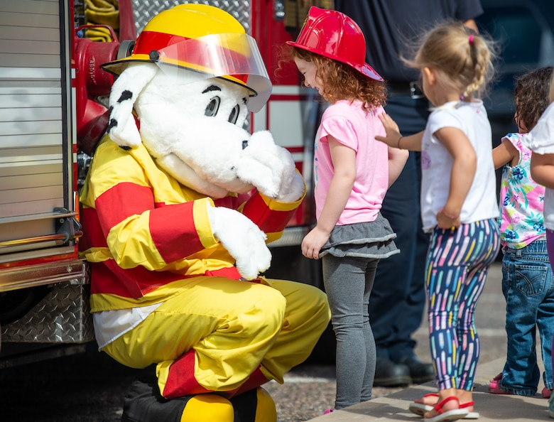"Children interact with ""Sparky the Fire Dog"" during a visit to the base library as part of Fire Prevention Week Oct. 3, 2018, at Luke Air Force Base, Ariz. This year's key message for Fire Prevention Week is, look, listen, and learn. (U.S. Air Force photo by Senior Airman Alexander Cook)"