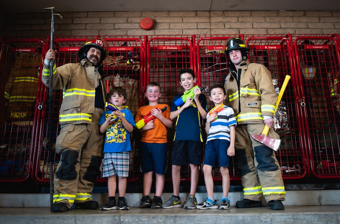Luke Air Force Base firefighters pose for a photo with children during a visit to the base fire station as part of Fire Prevention Week Oct. 3, 2018, at Luke AFB, Ariz. This year's theme for Fire Prevention Week encourages children to go toward a fire fighter during the event of a fire and not hide. (U.S. Air Force photo by Senior Airman Alexander Cook)