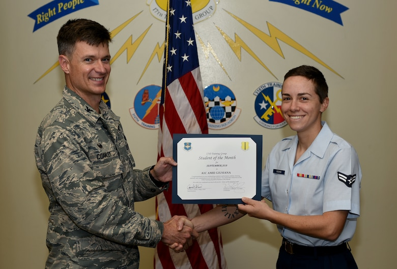 U.S. Air Force Col. Thomas Coakley, 17th Training Group commander, presents the 315th Training Squadron Student of the Month award to Airman 1st Class Amie Giusiana, 315th TRS student, at Brandenburg Hall on Goodfellow Air Force Base, Texas, Oct. 5, 2018. The 315th TRS's vision is to develop combat-ready intelligence, surveillance and reconnaissance professionals and promote an innovative squadron culture and identity unmatched across the U.S. Air Force. (U.S. Air Force photo by 2nd Lt. Matthew Stott/Released)