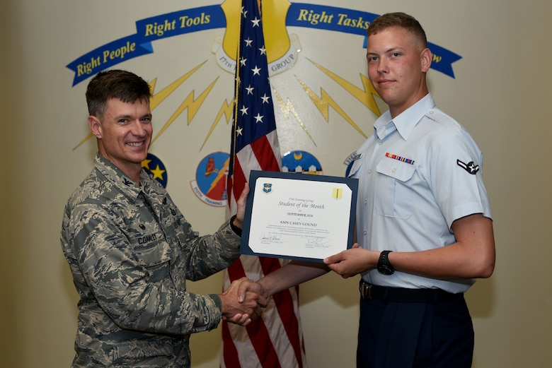 U.S. Air Force Col. Thomas Coakley, 17th Training Group commander, presents the 312th Training Squadron Student of the Month award to Airman Casey Gound, 312th TRS student, at Brandenburg Hall on Goodfellow Air Force Base, Texas, Oct. 5, 2018. The 312th TRS's mission is to provide Department of Defense and international customers with mission ready fire protection and special instruments graduates and provide mission support for the Air Force Technical Applications Center. (U.S. Air Force photo by 2nd Lt. Matthew Stott/Released)