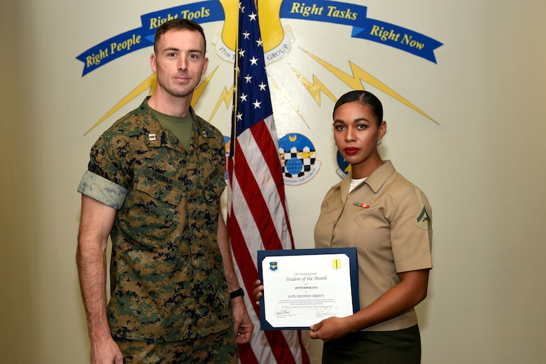 U.S. Marine Corps Capt. Jason Furman, Marine Corps Detachment at Goodfellow executive officer, presents the 316th Training Squadron Student of the Month award to Lance Cpl. Destiny Creecy, Marine Corps Detachment at Goodfellow student, at Brandenburg Hall on Goodfellow Air Force Base, Texas, Oct. 5, 2018. The 316th TRS's mission is to conduct U.S. Air Force, U.S. Army, U.S. Marine Corps, U.S. Navy and U.S. Coast Guard cryptologic, human intelligence and military training. (U.S. Air Force photo by 2nd Lt. Matthew Stott/Released)