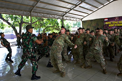 """Soldiers with the Indiana Army National Guard's 76th Infantry Brigade Combat Team and their Indonesian counterparts from the Tentara Nasional Indonesia army kick off Garuda Shield 18 by conducting a """"Yel-Yel,"""" a cry-and-response war dance, July 29, 2018, in Indonesia. Garuda Shield 18 is the third exercise in U.S. Army Pacific's second iteration of Pacific Pathways, a series of multinational engagements with ally and partner militaries in the Indo-Pacific region."""
